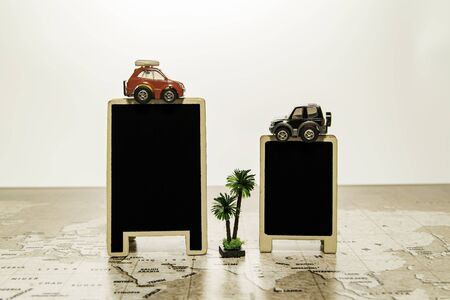 Two blank black boards with car on top on world map with palm tree Stock Photo