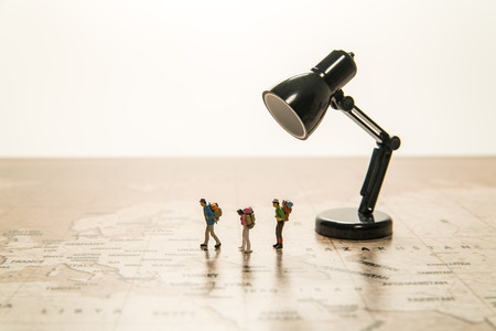 Three tiny human models walk on world map with lamp Stock Photo