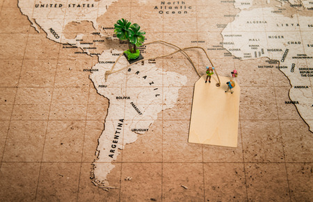 Tiny human models on price tag on world map with palm tree