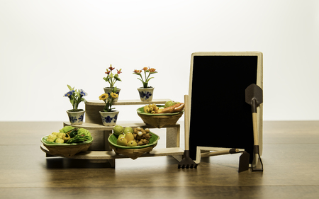 Fruits in the basket and flower on the shelf with blank black board and gardening tools