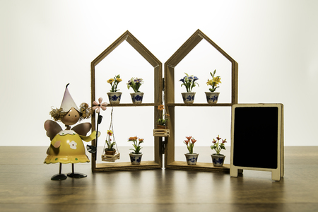 Yellow doll stand near the house frame with flower and blank black board