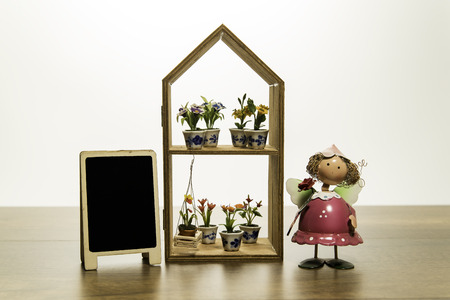 Girl doll stand near flowers on the shelf house frame with blank black board