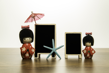 Two Japanese dolls with two blank black board with blue star fish and red umbrella