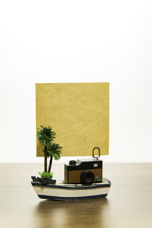 one wooden camera with blank yellow paper and palm tree on white boat