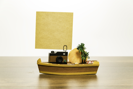 Camera with blank yellow paper on yellow boat with palm tree and shell fish
