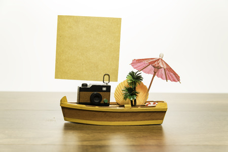 Camera with blank yellow paper on yellow boat with palm tree and shell fish and red umbrella