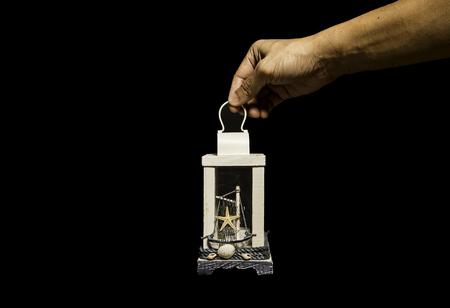 One hand holding white Sea style lantern isolated on black background