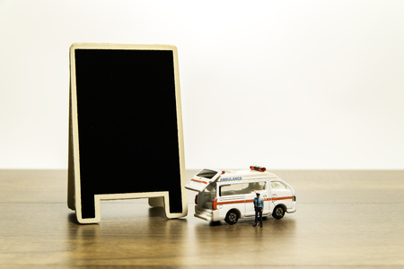 Blank black board near van ambulance and tiny police model Stock Photo