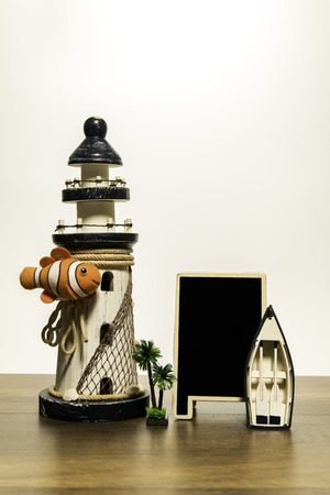 White Lighthouse with Crown fish and blank black board and boat