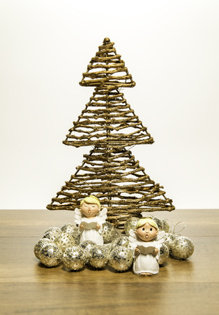 Two small angels stand in front of Christmas tree with silver balls Stock Photo