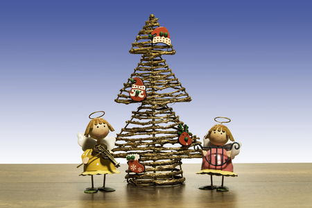Christmas tree with two angels play music instruments Stock Photo