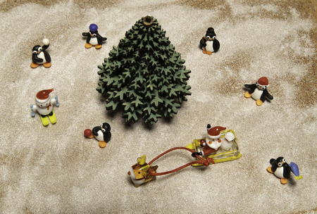 Santa in sleigh with reindeer run around green Christmas tree and many penguins and snow man Stock Photo