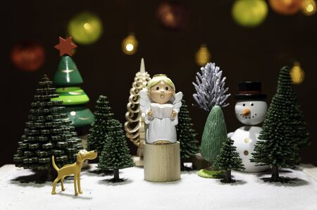 Small Angel read a book on circle wooden chair with dog watching and snow man isolated from Christmas light