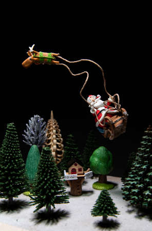 Santa Claus in sleigh with one Reindeer flying over house and trees