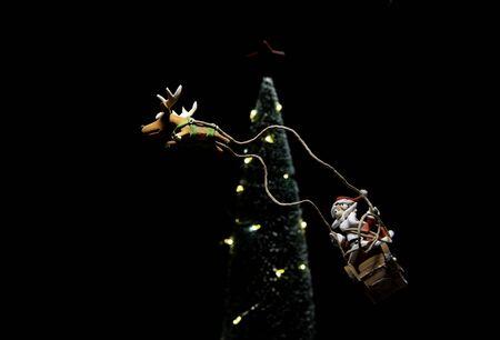 Santa Claus in sleigh with reindeer flying around Christmas tree