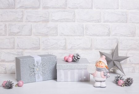 Christmas silver gifts with silver star, a toy, cones and pink balls on light gray brick horizontal background