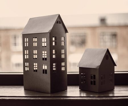 Paper black models of houses on window with bricked house