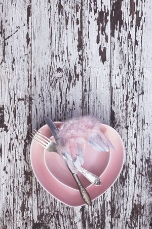 Pink plate in the shape of a heart with silver knife and fork and decorative wings on white wooden background. Top view. Love valentines day flat lay with copy space