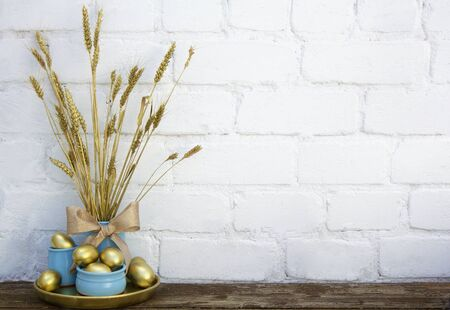 Easter decoration with gold eggs in blue pots with dry dyed wheat spikes on wooden table near white brick background. Horizontal, copy space. Place for text