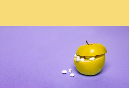 Medicine concept with fresh apple and tablets in its cut. Genetically modified fruit on purple and yellow background. Copy space, place for text, horizontal. Banco de Imagens