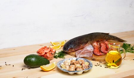 Seacuterie board with raw white fish, shrimps, squid, shellfish, langoustines and vegetables on light wood. Olive oil, lemon, and dill. Copy space Banque d'images