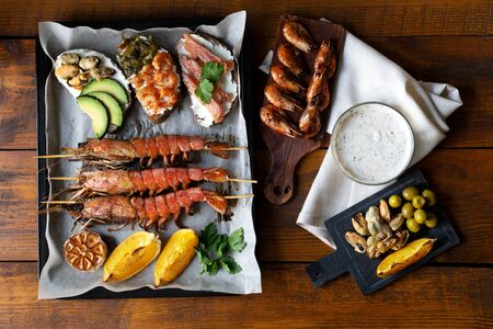 Seacuterie board with grilled langoustines on baking paper and black pan, sandwiches with seafood, avocado, red fish and sea kale, shrimps, mussels, lemon and white sauce on wood background. Top view