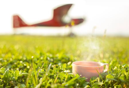 Zero waste travel cup with hot tea on green grass against defocused red small aircraft. Fresh spring meadow with drops on natural defocused sunlight green background. Horizontal Reklamní fotografie