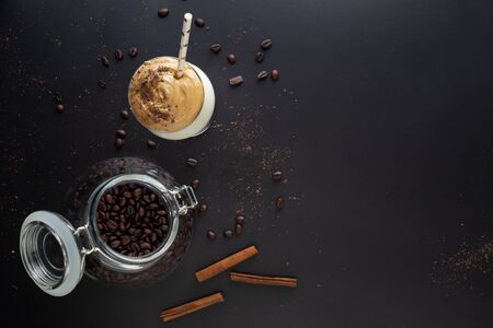 Dalgona coffee, a modern smooth, creamy and fluffy coffee with milk and ice with jar of coffee beans 스톡 콘텐츠