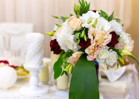 Bouquets of flowers on a festive wedding table in the restaurant. White, red and rose flowers with a candle. Horizontal
