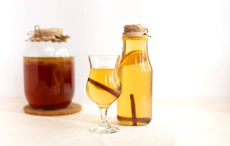 Homemade fermented raw kombucha tea with different flavorings. Healthy natural probiotic flavored drink with mushroom in glass jar, in bottle and in the glass on white background. Cinnamon and citrus Imagens