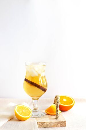 Homemade fermented raw kombucha tea with flavorings. Healthy natural probiotic drink in glass with orange and lemon on white background. Iced tea with cinnamon and citrus. Vertical, copy space
