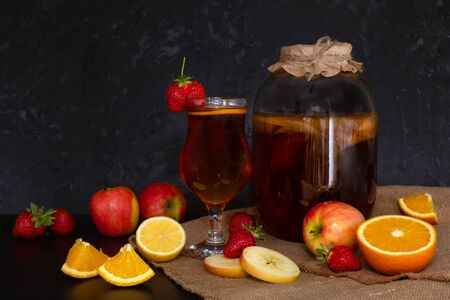 Homemade fermented raw kombucha tea with different fruit flavorings. Healthy natural probiotic flavored drink with mushroom in glass jar and in glass on dark background. Cinnamon, citrus, strawberry