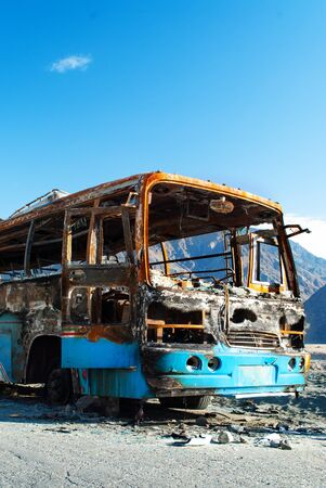 The frame of the burnt bus on the mountain road in Pakistan
