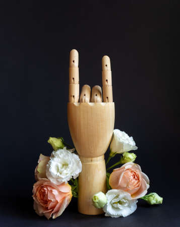 Wooden hand making Devils horns with flowers on black background