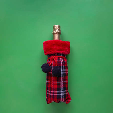 Champagne bottle in red and black checkered bag with pompons on green background. Minimal flat lay. Cozy new year party concept.