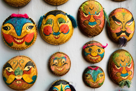 old quarter: Faces painted on woven round bamboo trays hanging in shops throughtpot the narrow winding lanes of Hanoi