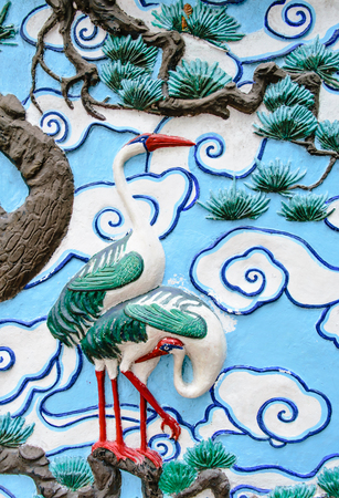 bas relief: Bas relief sculpture of crane on the tree with cloud background Stock Photo