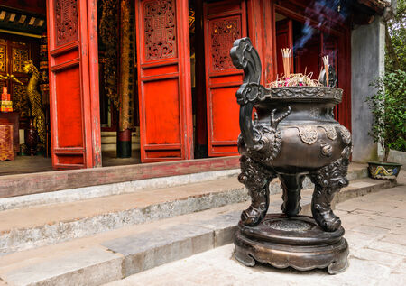 red door: Chinese joss stick pot in front of red door of chinese temple in Hanoi, Vietnam
