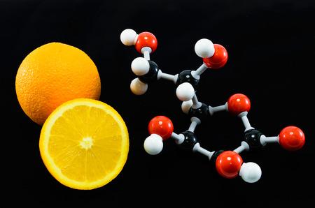 scurvy: Orange and vitamin C structure model (Ascorbic acid) on black background for education