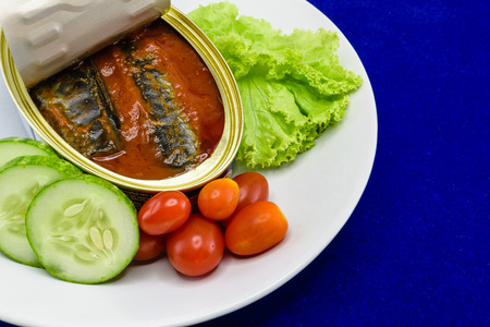 canned meat: Canned Sardine fish in tomato sauce served on dish with salad for the concept of quick meal or healthy food (omega-3) Stock Photo