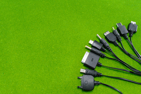 Multi-heads of mobile phone charger (Universal charger) on green background photo