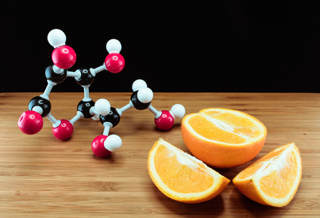 Orange and vitamin C structure model (Ascorbic acid) on wood with black background Stock Photo