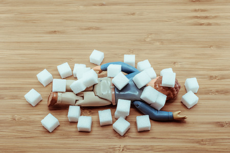 Drop Dead doll man under falling sugar cubes for the concept of high blood sugar, obesity, diabetic Stok Fotoğraf