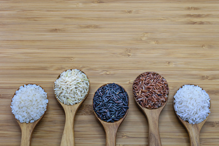 Variety of rice in wood spoon on wood background. From left: Japanese rice, pounded brown rice, forbidden rice (riceberry), pounded red rice, jasmine rice