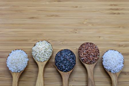 Verscheidenheid van rijst in houten lepel op houten achtergrond. Van links naar rechts: Japanse rijst, bonsde bruine rijst, verboden rijst (riceberry), bonsde rode rijst, jasmijn rijst Stockfoto