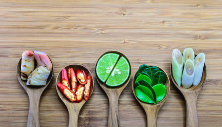 Essential ingredients of Tom Yum, Thailand fomous food in wood spoon on wood background. From left: Galangal, Chili lime,  kaffir lime leaves, lemongrass photo