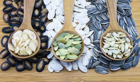Edible seeds in wood spoon on wood background; From left, watermelon seed, pumpkin seed, sunflower seed