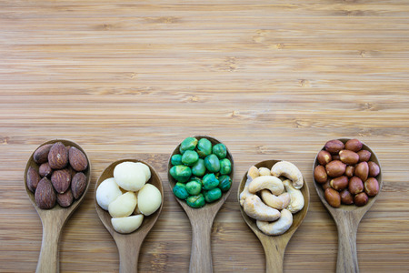 Mixed nuts in wood spoon on wood background, From left-Almond, Macadamia, Green Peanuts, Cashew nut, Skin red peanuts photo