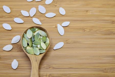 Edible pumpkin seeds in wood spoon on wood background