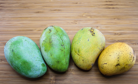 ripening: Ripening stage of mango on wood background Stock Photo